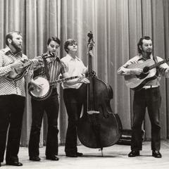 Four man band playing a concert in theater