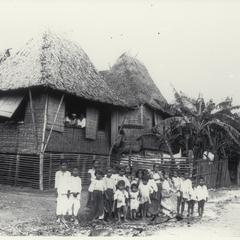 Native children in front of Tagal tribe-bamboo houses, Manila, early 1900s