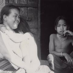 Nyaheun mother seated with two daughters on porch in Houei Kong Cluster in Attapu Province