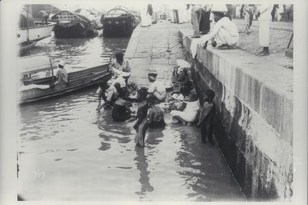 Filipinos washing clothes and bathing in river, 1900s