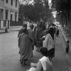 Young novices receiving food from lay women, child in right background