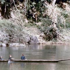 Hmong boys paddling a canoe on a river in Houa Khong Province
