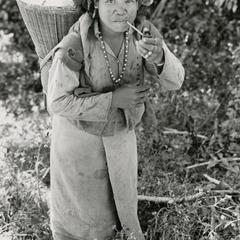 A Nyaheun woman walks and smokes a pipe in Attapu Province