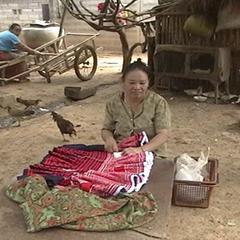 Woman making a paj ntaub skirt