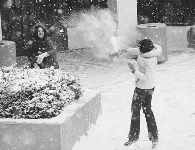 Two female students in snowball fight