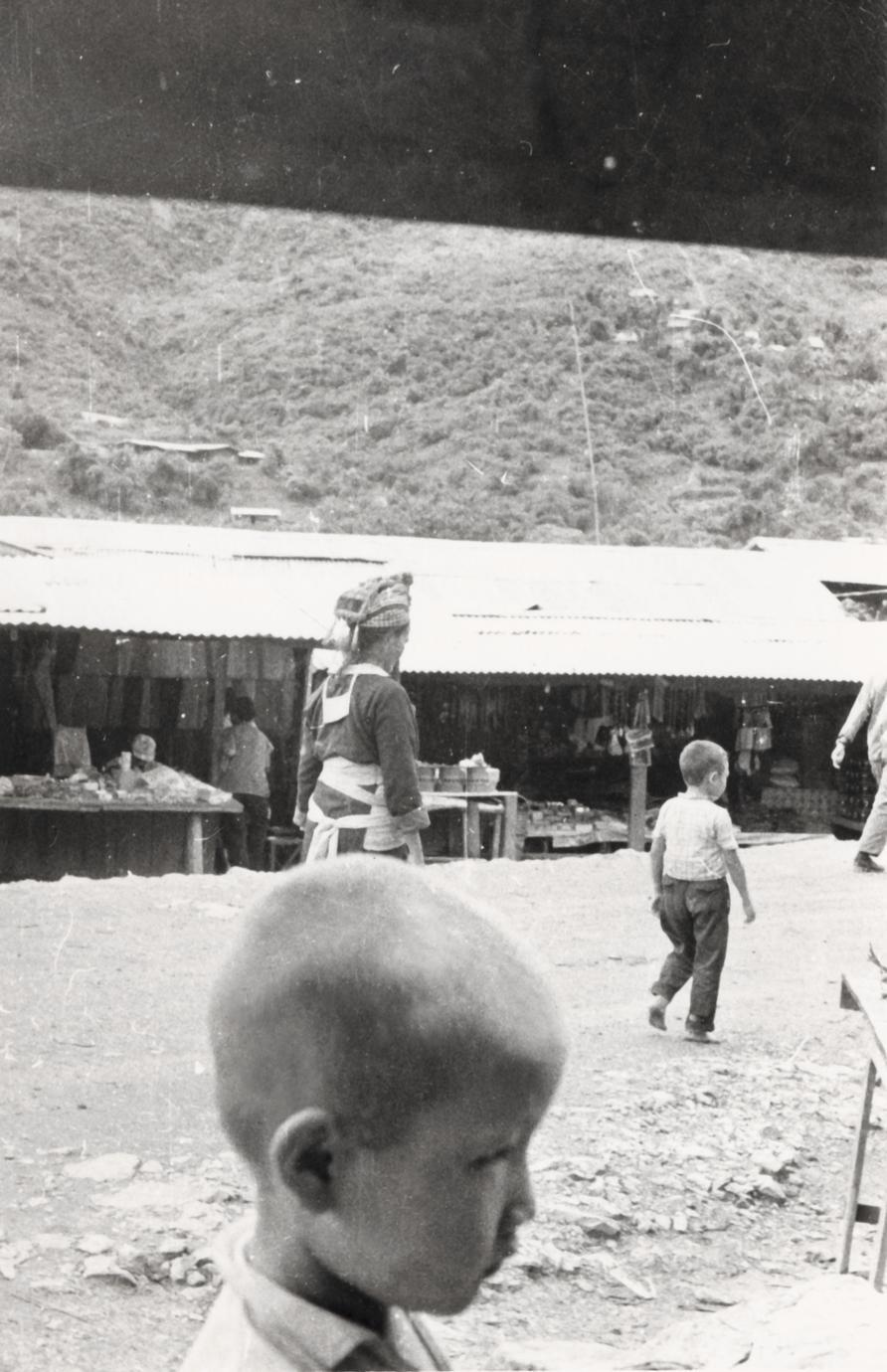 A White Hmong woman walks near a market in Xiang Khoang Province