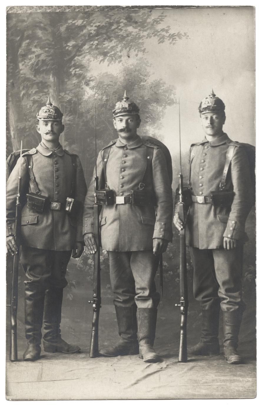 [Group portrait of three soldiers holding rifles with bayonets affixed]