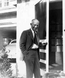 On the stoop of the family home in Madison, Wisconsin, door open and car visible in garage at left, ca. 1944