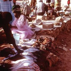 Woman Merchant Wearing Typical Senegalese Dress in Fish Market at the Beach of Soumbedioune
