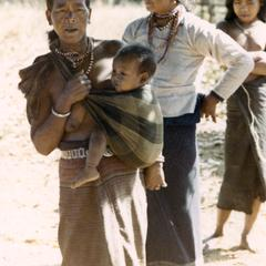 Nyaheun mother and child stand in a village in Attapu Province