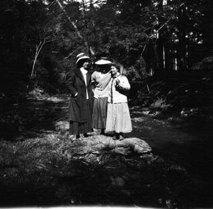 Three women standing on rock near river