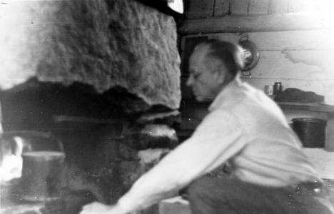 Aldo Leopold by shack fireplace