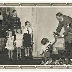 [Hitler receives gift of flowers from saluting Hitler youth and children]