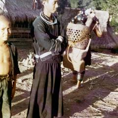 Akha young man stands in traditional dress in the village of Phate in Houa Khong Province