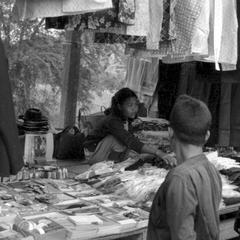 Woman merchant displaying notions and clothing at morning market
