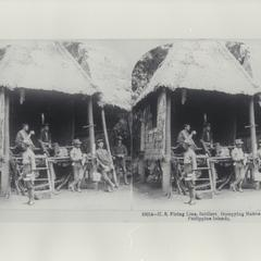 U.S. soldiers relax in a thatched hut, 1899