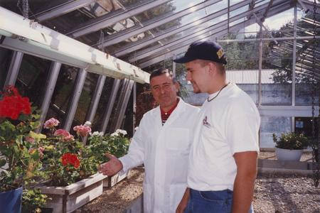 Biology professor Sami Saad with student in greenhouse