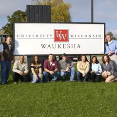Staff and students pose in front of UW-Waukesha sign