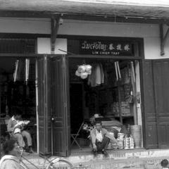 Two adjoining shops selling housewares, sign in Lao, Chinese and French