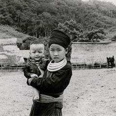 A Blue Hmong (Hmong Njua) girl holds her little brother in a village in Muang Vang Vieng in Vientiane Province