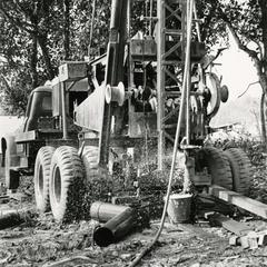 Well drilling rig drills new well in a village in Houa Khong Province