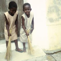 Girls in School Uniforms Cleaning House Entryway