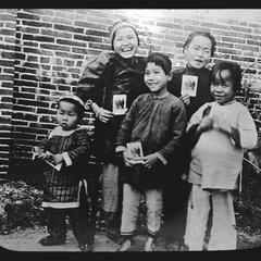 [Children holding photos]
