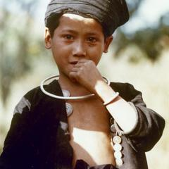 An Akha Burmese refugee boy stands in traditional clothing in Houa Khong Province