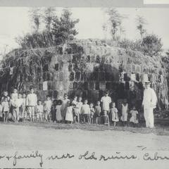 Mr. Baylor posing with children near old ruins, Cebu