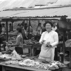 Vietnamese woman selling meat at morning market, Vietnamese-style hat on corrugated tin roof in background