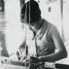 A Lao woman weaves on her handloom in her village near the town of Vang Vieng in Vientiane Province