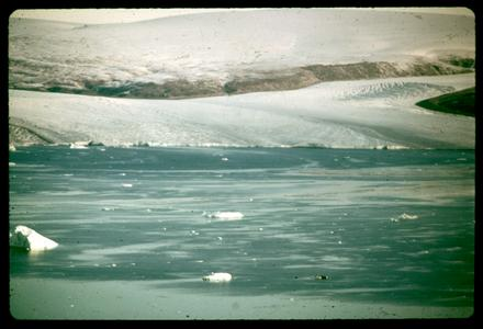 Edge of a glacier with frozen meltwater in foreground
