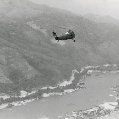 A H-34 helicopter flies over the mountains and Mekong River in Houa Khong Province