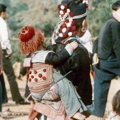 A White Hmong mother carries her child in Houa Khong Province