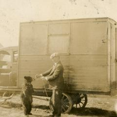 Frank Hall with bear in front of circus truck