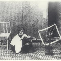 Woman spinning thread with a wooden spinning wheel, 1900s