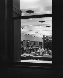 Students studying seen through a window
