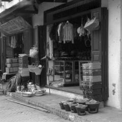Shop displaying wares in front, suitcases, charcoal braziers, enameled ware, teapots, bags, two shops have similar products