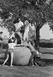 Students standing on Earth Ball on university grounds