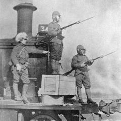 Three Japanese soldiers on a railway engine.