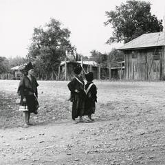 One Blue Hmong woman and two Yao women stand on a road in the town of Xaignabouri in Xaignabouri Province