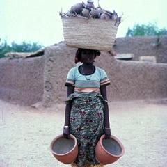 Hausa Potter Carries Her Pots to Kiln to be Fired