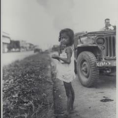 Starved child waiting for rations after bombing, Manila, 1945