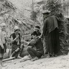 Akha villagers at Phate prepare thatched roofing in Houa Khong Province