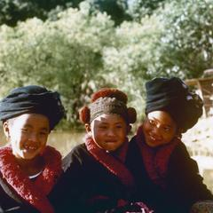 Three Yao (Iu Mien) girls are seated near a pond at in Houa Khong Province