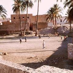 Boys Play Soccer Near Houses