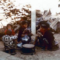 Five Yao (Iu Mien) children are seated and eating in the town of Nam Kheung in Houa Khong Province