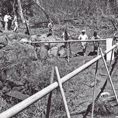 The District Chief and villagers inspect the pipes that carry the water to Houei Kong in Attapu Province