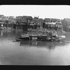 Chinese houses on stilts and river boats.
