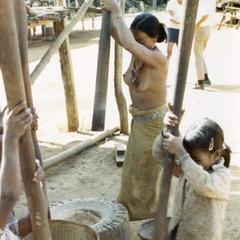 Nyaheun women and girl are pounding rice in a village in Attapu Province